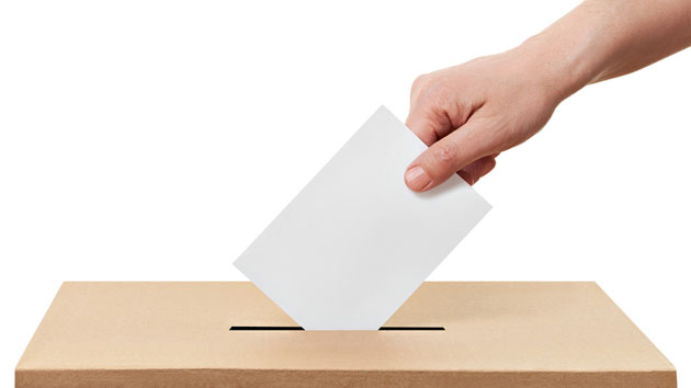 Main qui dépose un buletin de vote dans une urne